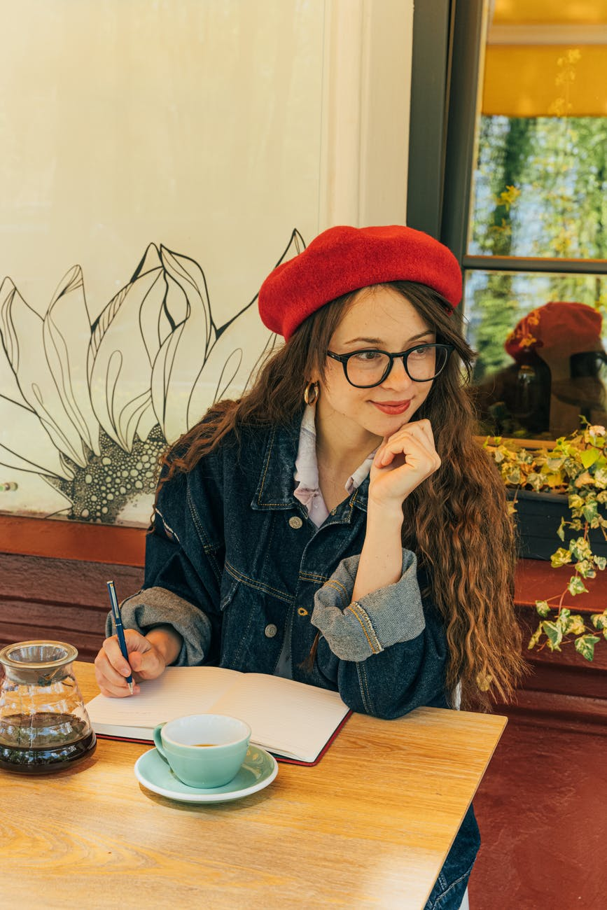 woman in blue denim jacket wearing red knit cap sitting at table